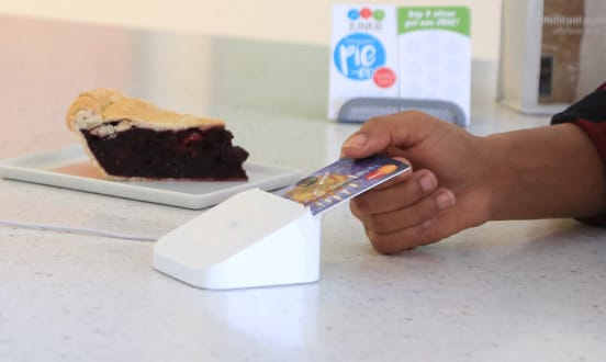 Hand inserting rewards card into chip card reader to pay for pie