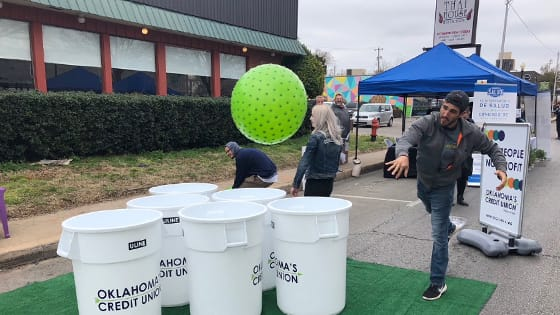 Man playing OKCU's Giant Pong at Open Streets in Uptown 23rd district